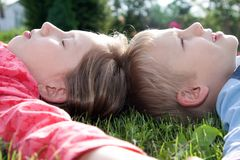 Boy and girl laying on grass Stock Photos