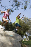 Boy (6-8) and girl (12-14) leaping from rock in park, smiling, low angle view Royalty Free Stock Image