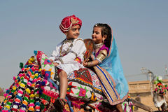 Boy and girl like a royal family drive to the Desert Festival. JAISALMER, INDIA: Boy and girl like a royal family sitting on the camel back and drive to the Stock Photos