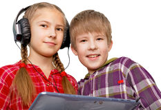 Boy and girl are listening to music on tablet PC Royalty Free Stock Photos