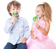 Boy and girl with lollipops stock images
