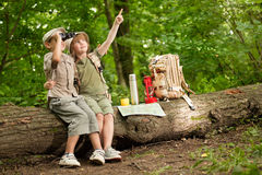 Boy and a girl looking at birds through binoculars, camping in t. Excited children on a camping trip in green forest stock photo