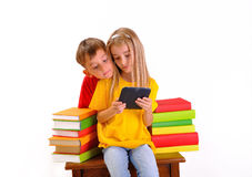 Boy and girl looking e-book surrounded by books
