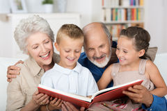 Boy and girl looking at a photo album. Cute boy and girl sitting in the lap of their grandparents and looking happily together at a photo album Royalty Free Stock Photos