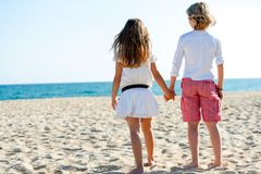 Boy and girl looking at sea. Cute boy and girl holding hands looking at sea Royalty Free Stock Photos