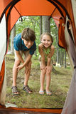 Boy and girl looking into tent Stock Photo