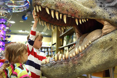 Boy and girl looking in tyrannosaurus opened mouth Stock Photo