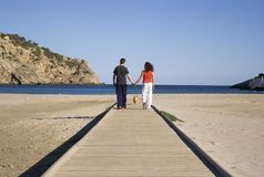 Boy and Girl in love walking. Young couple in love walking the dog on the beach Stock Photos