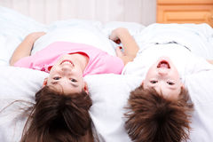 Boy and girl lying on bed Stock Photography