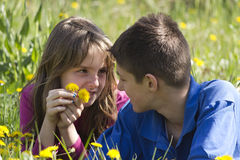 Boy and girl lying in a field of dandelion Royalty Free Stock Photography