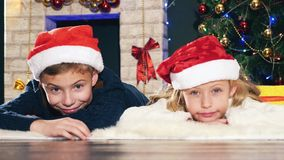 Boy and girl lying on the floor near Christmas tree stock footage