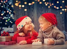 Boy and girl lying on the floor with presents near christmas tree Stock Photography