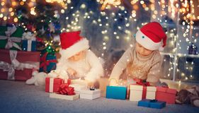 Boy and girl lying on the floor with presents near christmas tree Royalty Free Stock Image