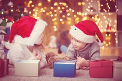 Boy and girl lying on the floor with presents near christmas tree stock images