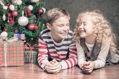 Boy and girl lying on the floor under Christmas tree Stock Image
