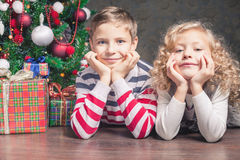 Boy and girl lying on the floor under Christmas tree Stock Images