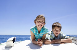 Boy and girl (8-10) lying on front on deck of sailing boat out at sea, side by side, smiling, front view, portrait Royalty Free Stock Photo