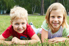 Boy and girl lying on green grass Royalty Free Stock Image