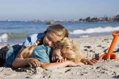Boy (4-6) and girl (7-9) lying on sandy beach beside orange spade, smiling, side view Royalty Free Stock Images