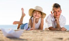 Boy and girl lying on sandy beach Stock Photography