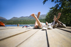 Boy and girl (7-10) lying side by side on lake jetty, shoes off, rear view (surface level) Stock Photos