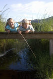 Boy (6-8) and girl (7-9) lying on small wooden footbridge above stream, holding sticks, smiling, portrait Royalty Free Stock Photography