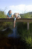 Boy (6-8) and girl (7-9) lying on small wooden footbridge above stream, holding sticks, smiling, portrait Royalty Free Stock Photos