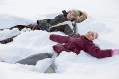 Boy and girl lying in the snow. And smiling royalty free stock photos