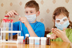 Boy and girl make chemical experiments Stock Images