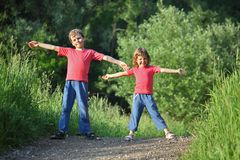 Boy and girl make gymnastic in park. Summer Stock Images