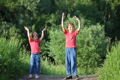 Boy and girl make gymnastic in park. Summer Stock Photo