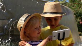 Boy and a girl take a selfie photo at the fountain. Boy and girl make selfie photo on the background of the fountain stock video footage