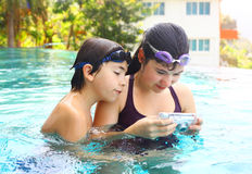Boy and girl make underwater camera shoot. Teen siblings boy and girl brother and sister make underwater camera shoot footage in the open air swimming pool in Stock Photography