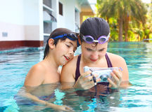 Boy and girl make underwater camera shoot. Teen siblings boy and girl brother and sister make underwater camera shoot footage in the open air swimming pool in Royalty Free Stock Image