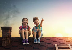 Boy and girl make a wish. Two cute children sit on the roof and look at the stars. Boy and girl make a wish by seeing a shooting star Stock Photo