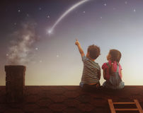 Boy and girl make a wish. Two cute children sit on the roof and look at the stars. Boy and girl make a wish by seeing a shooting star stock photos