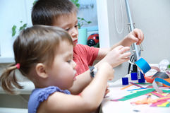 Boy and girl making craft with paper with glue Stock Image