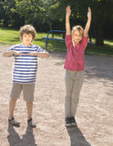 Boy and girl making physical excersises. Boy and girl Caucasian making physical excersises on yard in summer Royalty Free Stock Images