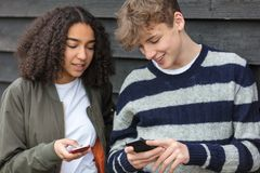 Boy Girl Male Female Teenagers Using Cell Phone. Interracial teenagers boy and girl, male and female, mixed race African American girl, Caucasian boy,  texting Royalty Free Stock Photo