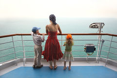 Boy and girl with mother standing on ship deck. Little boy and girl with mother standing on ship deck and looking at horizon Royalty Free Stock Images