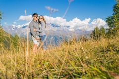 A boy with a girl in the mountains in the background of summer mountains of rocky landscape with trees. Sitting on the. Grass. Tenderness kisses love Royalty Free Stock Image