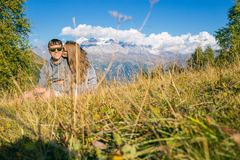 A boy with a girl in the mountains in the background of summer mountains of rocky landscape with trees. Sitting on the. Grass. Tenderness kisses love Stock Photo