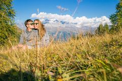 A boy with a girl in the mountains in the background of summer mountains of rocky landscape with trees. Sitting on the. Grass. Tenderness kisses love Royalty Free Stock Photo