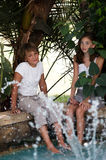 Boy and girl near fountain . Children near the fountain surrounded by tropical plants royalty free stock images