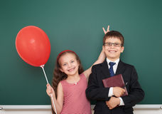 Boy and girl near school board Stock Photos