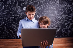 Boy and girl  with notebook against big blackboard, school Royalty Free Stock Photos