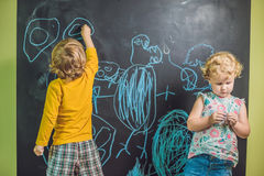 Boy and girl paint with chalk on a blackboard Stock Photography