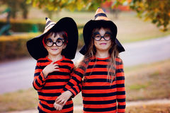 Boy and girl in the park in halloween costumes, having fun Royalty Free Stock Photos