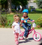 Boy and girl in park learning to ride a bike. Happy childrens outdoor,  brother and sister in park have fun. Boy and girl in park learning to ride a bike Royalty Free Stock Photo