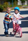 Boy and girl in park learning to ride a bike Stock Photos